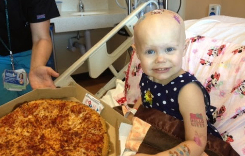 Little girl with Pizza in hospital bed