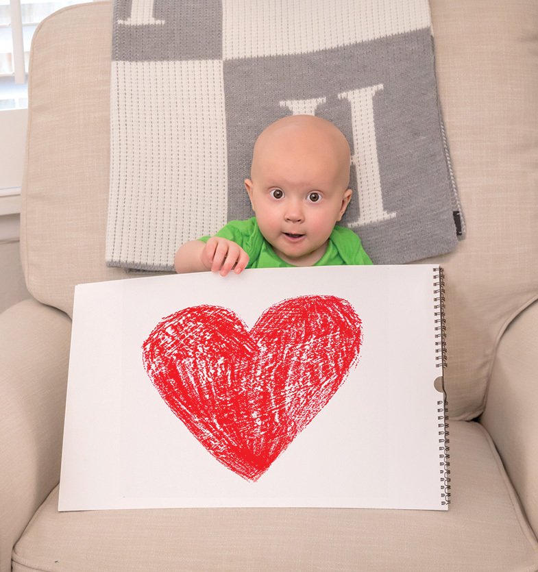 toddler holding up heart