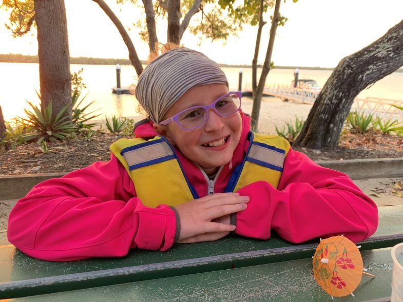 Hannah in a life-vest near the beach