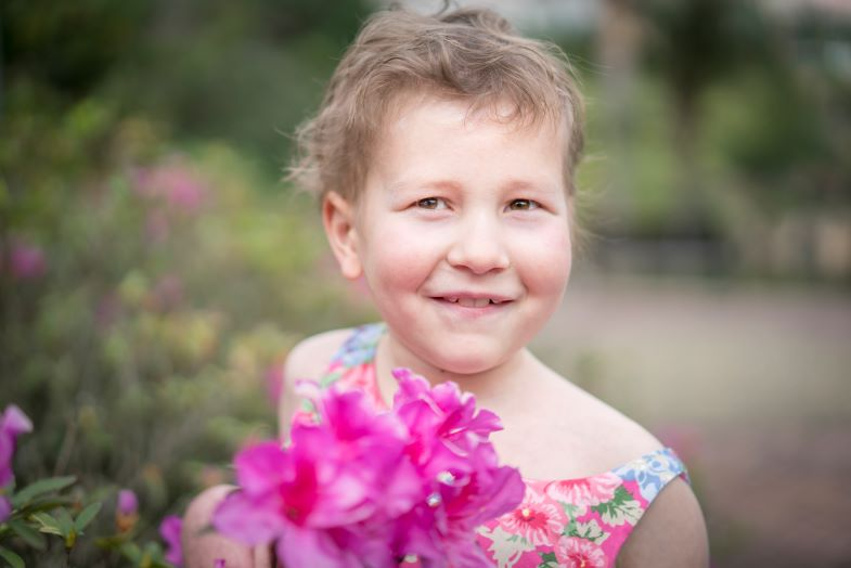 A younger Hannah smiling, with a flower