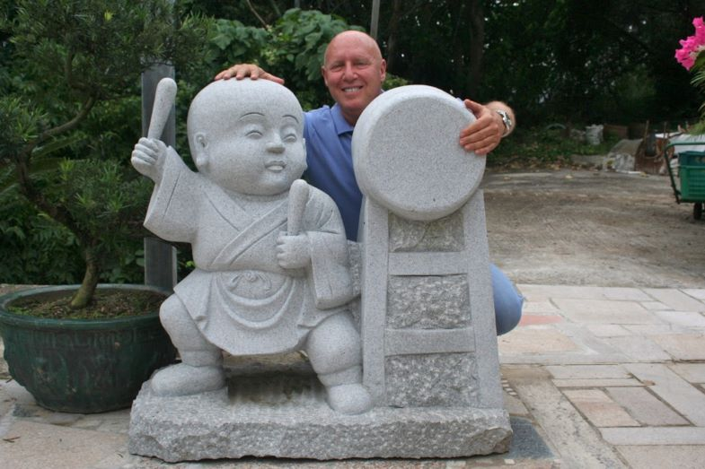 Richard Kligler poses with a Buddha statue at the Ten Thousand Buddhas Monastery in Hong Kong