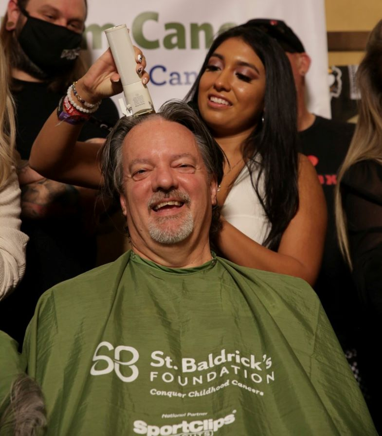 Erin Ralston shaves the head of Phil Ralston, her father, during the St. Baldrick's Foundation event at McMullan's Irish Pub on Saturday, Sept. 18